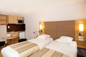 A bed or beds in a room at Séjours & Affaires Strasbourg Kleber