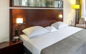 A bed or beds in a room at Dorint Am Goethepark Weimar