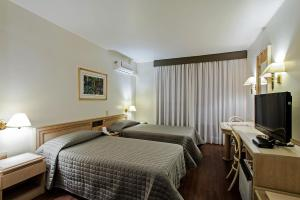 A bed or beds in a room at Trevi Hotel e Business