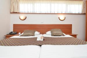 A bed or beds in a room at Hotel Neboder