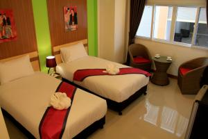 A bed or beds in a room at Panmanee Hotel