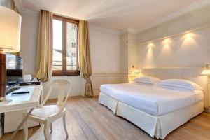 A bed or beds in a room at Grand Hotel Cavour