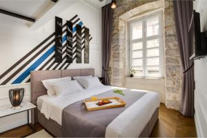 A bed or beds in a room at DeZign Superior Apartments & Rooms