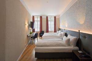 A bed or beds in a room at Altstadt Hotel Krone Luzern