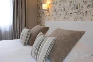 A bed or beds in a room at Logis Hôtel du Centre - Halte en cyclotourisme avec garage à vélos clos