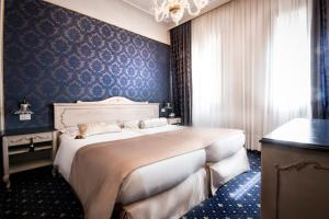 A bed or beds in a room at Hotel Violino d'Oro