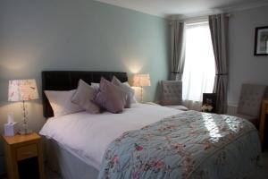 A bed or beds in a room at The Oak House Hotel