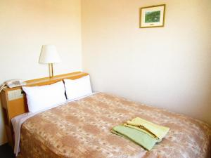 A bed or beds in a room at Green Hotel Omagari