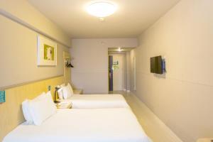 Кровать или кровати в номере Jinjiang Inn Shenyang Army General Hospital