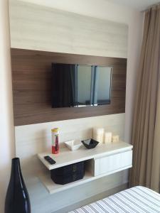 Uma TV ou centro de entretenimento em Apartamento Futurum no Vg Fun Residence