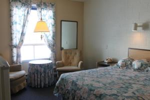 A bed or beds in a room at Auberge - Motel Le Pigeonnier