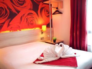 A bed or beds in a room at Brit Hotel Essentiel de Granville