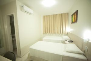 A bed or beds in a room at Hotel Itajaí Tur