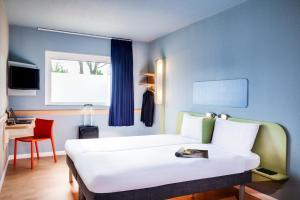 A bed or beds in a room at ibis budget London Barking