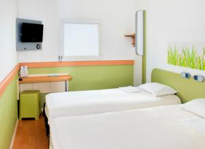 A bed or beds in a room at Ibis Budget Clermont Ferrand - Le Brezet - Aeroport