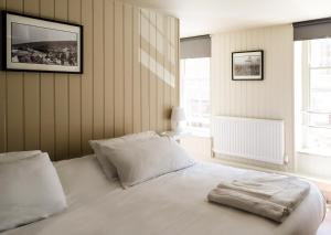 A bed or beds in a room at The Wheatsheaf Hotel
