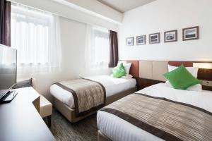 A bed or beds in a room at HOTEL MYSTAYS Shin Osaka Conference Center