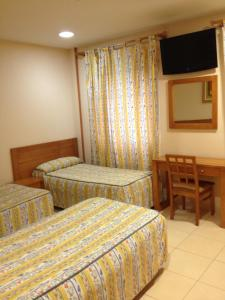 A bed or beds in a room at Hostal Aeropuerto