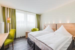 A bed or beds in a room at Novina Hotel Wöhrdersee Nürnberg City