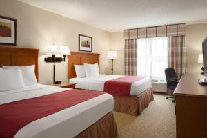 A bed or beds in a room at Country Inn & Suites by Radisson, Toledo South, OH