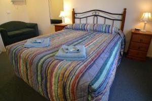 A bed or beds in a room at Parkhaven Motel