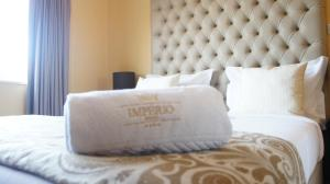 A bed or beds in a room at Hotel Império