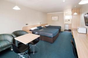 A bed or beds in a room at Box Hill Motel