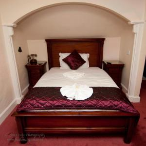 A bed or beds in a room at The Old Manor House Hotel