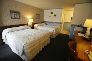 A bed or beds in a room at Bennington Motor Inn