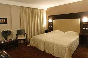 A bed or beds in a room at Alassia Hotel
