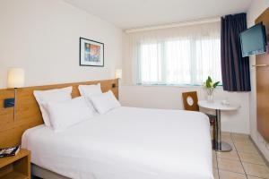 Кровать или кровати в номере Séjours & Affaires Serris Rive Gauche