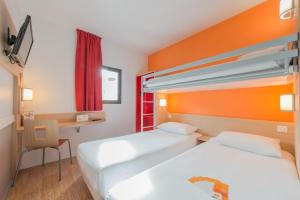 A bed or beds in a room at Première Classe La Rochelle Centre - Les Minimes