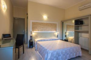 A bed or beds in a room at Hotel Calamosca