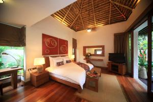 A bed or beds in a room at The Banjaran Hotsprings Retreat