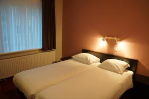 A bed or beds in a room at Hotel Du Soleil