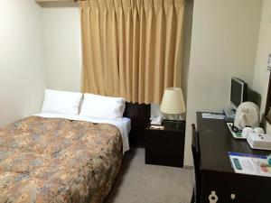 A bed or beds in a room at Hotel Crown Hills Toyama