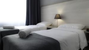 A bed or beds in a room at Fili House Hotel