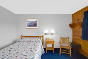 A bed or beds in a room at Super 8 by Wyndham Lake George/Warrensburg Area