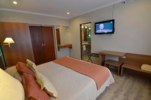 A television and/or entertainment center at Alto Verde Suite & Apart