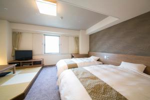A bed or beds in a room at Nagoya Kasadera Hotel
