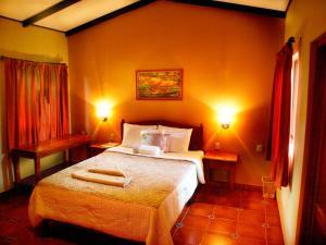 A bed or beds in a room at El Encanto Garden Hotel