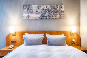 A bed or beds in a room at Leonardo Hotel Aachen