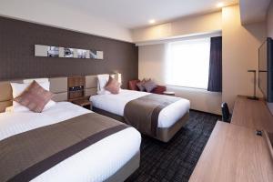 A bed or beds in a room at HOTEL MYSTAYS Yokohama Kannai