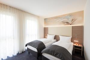 A bed or beds in a room at Book Hotel Leipzig