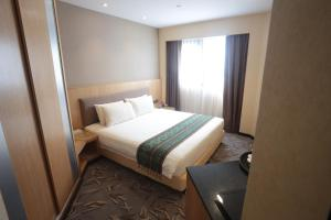 A bed or beds in a room at Imperial Riverbank Hotel Kuching