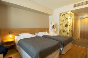 A bed or beds in a room at Spa Hotel Peurunka