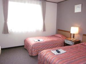 Tempat tidur dalam kamar di Ayun Takayama Central Hotel