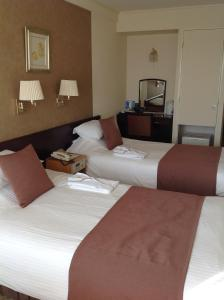 A bed or beds in a room at Okayama Plaza Hotel