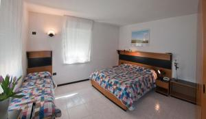 A bed or beds in a room at Albergo Alla Torre