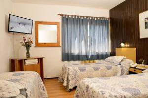 A bed or beds in a room at Hotel Antártida